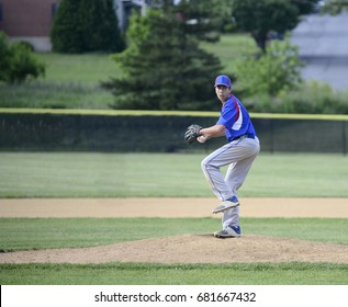 Teenage baseball pitcher winding up on the pitchers mound.