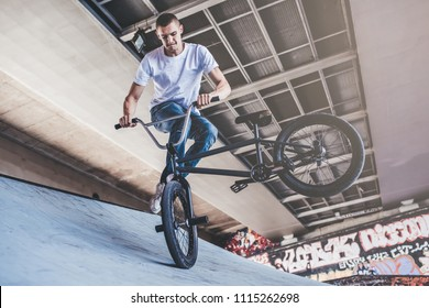 Teenage BMX rider is performing tricks in skatepark.