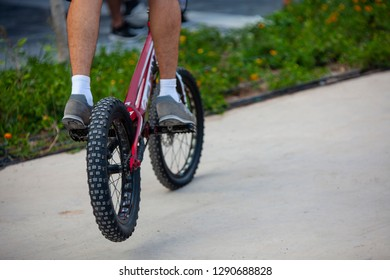 Teenage Bmx rider is performing tricks in skatepark. Bmx rider riding on a front wheel of a bicycle.