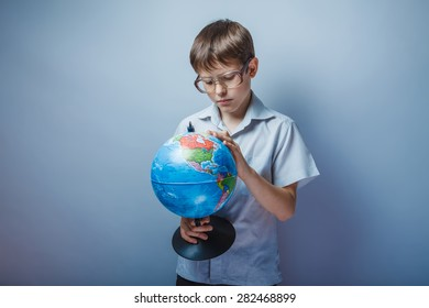 Teenage boy about ten years old European appearance in a light brown shirt and glasses consider globe on gray background, curiosity, knowledge
