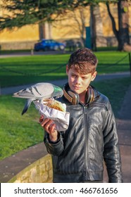 Teenage boy absorbed in feeding the pigeon