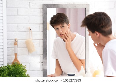 Teenage boy with acne problem looking in mirror at home