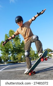 Teenage boy balancing on a skateboard in a parking lot on a sunny day with blue sky and trees in the background.