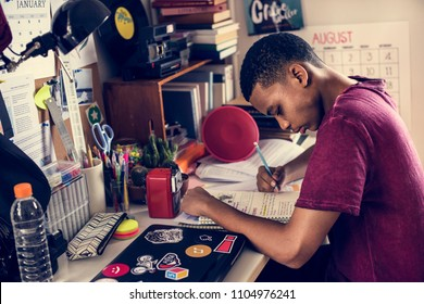 Teenage boy in a bedroom doing work stressed out and frustrated