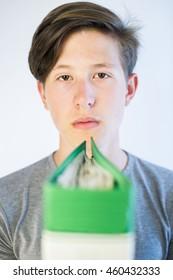 Teenage boy behind a green school binder.
