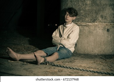 Teenage boy being kept captive in an attic tied around the ankle by a thick rope and constrained in a straight jacket in shadowy darkness