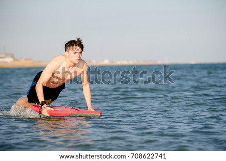 Teenage boy with a body board in the sea