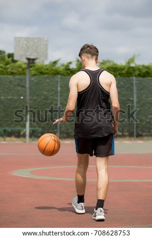 Teenage boy bouncing a basketball on a court