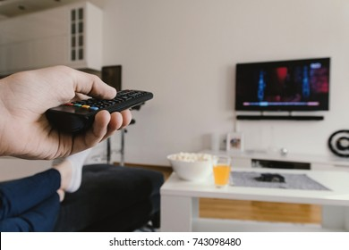 Teenage Boy changing channel. Watching tv and using remote control. Using the remote control to change channesl on Tv