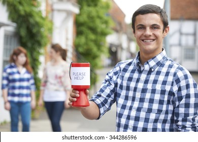 Teenage Boy Collecting For Charity In Street
