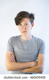 Teenage boy with crossed arms and angry and unsatisfied look.