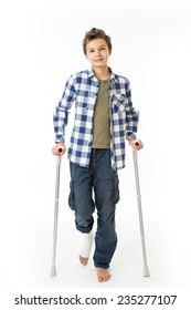 Teenage Boy with crutches and a bandage on his right leg, isolated against white