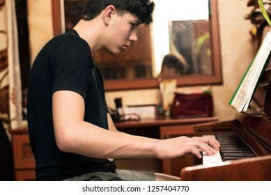 A teenage boy with dark hair plays a piano at home. The guy looks at notes and studies a new musical composition. Focus on hands