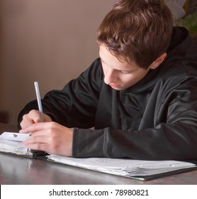 Teenage boy in deep concentration doing his homework
