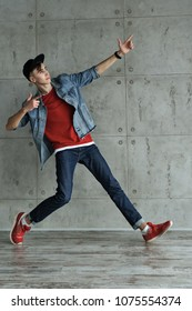 Teenage boy in denim jacket and baseball cap, jeans and red sweater dances hip-hop. Dynamics of modern dance movement