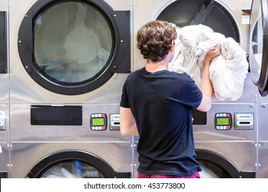 Teenage boy doing the laundry in a public laundromat.