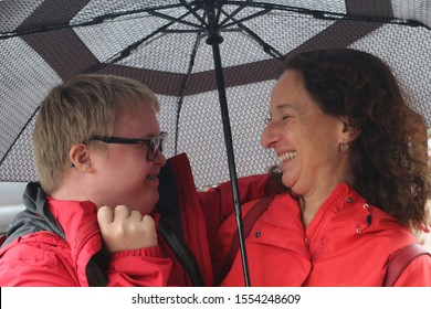 Teenage boy with Down Syndrome with his mom under an umbrella on a rainy day