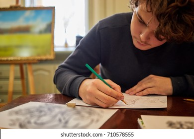 Teenage boy draws picture sitting at table in room.