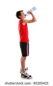 A teenage boy dressed in sports wear is drinking water from a bottle.  White background.