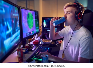 Teenage Boy Drinking Caffeine Energy Drink Gaming At Home Using Dual Computer Screens At Night