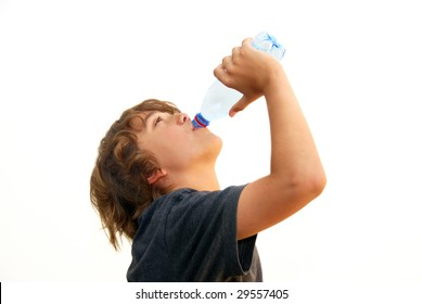 Teenage boy drinking water from a plastic bottle isolated on white background.