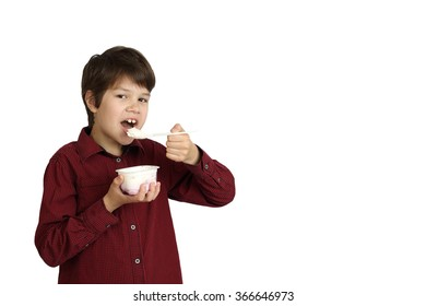 Teenage boy eats yogurt isolated on white background with copy space for text or advertising