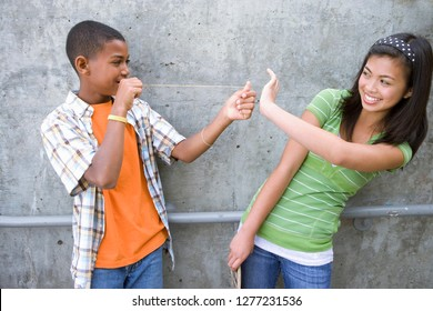 Teenage boy flicking rubber band at girl outdoors