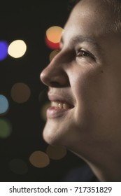 Teenage Boy in front of Christmas Lights, taken in a dark room with Colorful Bokeh in the Background