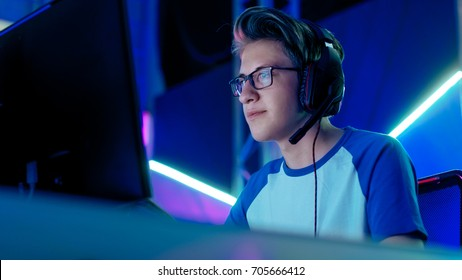 Teenage Boy Gamer Plays in Competitive Video Game on a eSports Tournament/ Internet Cafe. He Wears Glasses and Headphones with Microphone.
