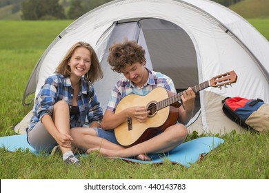 Teenage boy and girl near the tent playing a guitar while sitting on a green grass