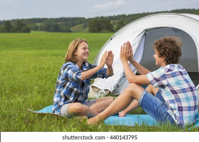 Teenage boy and girl near a white tent on the green grass in the summer