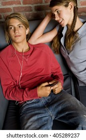 Teenage boy and girl seated, boy listening to music on mp3