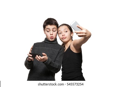 Teenage boy and girl with their smart phone, she making self portrait, isolated on white background