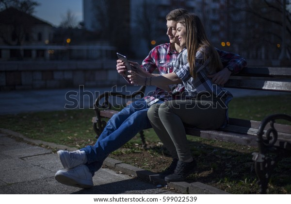 Teenage boy and girl using tablet in park