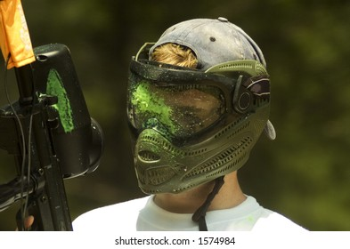 A teenage boy with green paint on his facemask from a direct hit with a paintball.