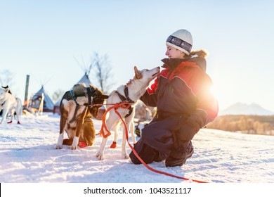 Teenage boy having a cuddle with husky sled dog in Northern Norway