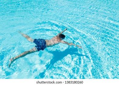 Teenage boy having joy in blue water of swimming pool.