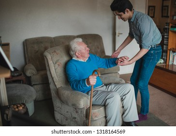 Teenage boy is helping his grandfather out of his armchair.