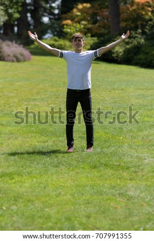 Teenage boy with his arms outstreched on a summer's day