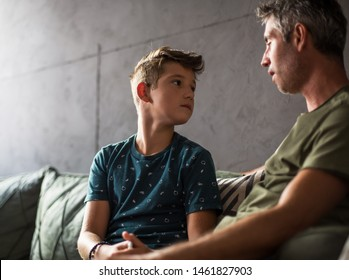 Teenage boy and his father talking