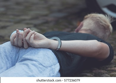 Teenage boy with his hands cuffed behind his back lying on the ground near a car after being apprehended for a misdemeanor or crime with focus to his hands