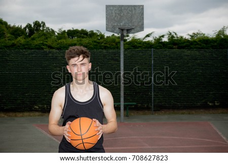 Teenage boy holding a basketball on a court