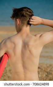 Teenage boy holding a body board on a beach