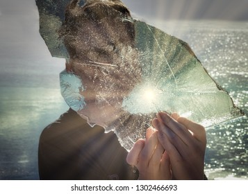 A teenage boy holds a large piece of ice from the lake with water dripping down his fingers. Sun rays reflect from the ice and the water in the background.