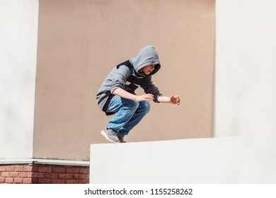 Teenage boy in the hood on a street in a big city next to a high-rise building alone. concept of a teenager parkour life. parkour jump portrait on the street in the big city close up view