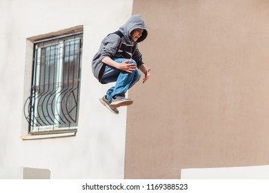 Teenage boy in the hood on a street in a big city next to a high-rise building alone. concept of a teenager parkour life. parkour jump portrait on the street in the big city close