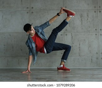 Teenage boy in jeans and red sweater, denim jacket and baseball cap dances of break dance. Dynamics of modern dance movement. Youth fashion.