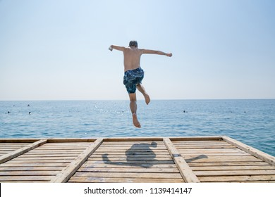 Teenage boy, jumping into the sea from wooden jetty on a beach. Happy summer vacation concept.
