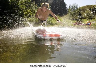 Teenage boy jumping on airbed
