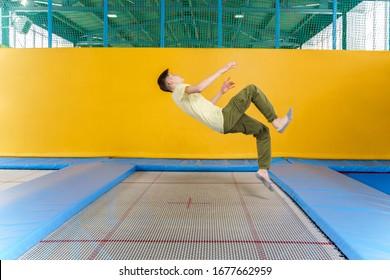 Teenage boy jumping on trampoline park in sport center
